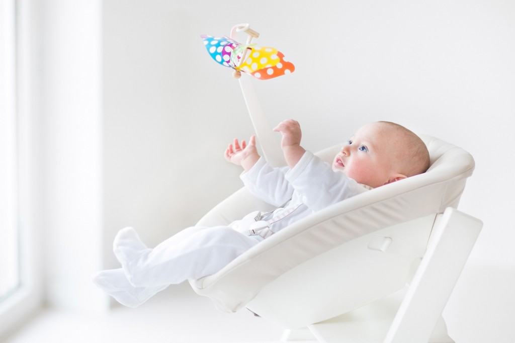 Cute newborn baby boy watching a colorful mobile toy sitting in a white chair next to a window